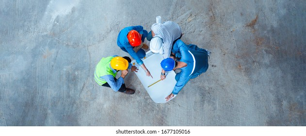 Top view of architectural engineer working on his blueprints with documents on construction site. meeting, discussing,designing, planing