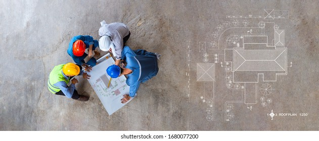 Top view of architectural engineer working on his blueprints with documents on construction site. meeting, discussing,designing, planing, roof plan
