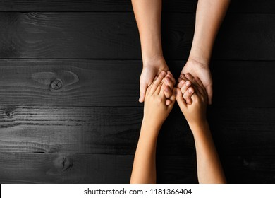 top view arms stretches out and holds one another on black wooden background. joint support and assistance in the community, children's hands help each other with support