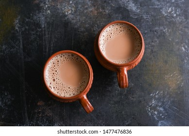 Top view of aromatic Indian milk tea or masala Chai, brewed hot herbal or spiced, in Kerala India. Two cups of organic ayurvedic drink herbal tea is good in winter for immunity and health, antistress.