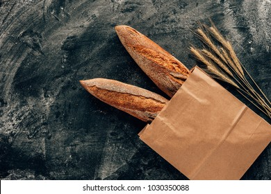 top view of arranged french baguettes in paper bag and wheat on dark tabletop with flour