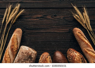 top view of arranged loafs of bread and wheat on wooden surface