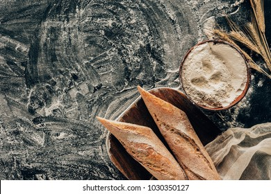 top view of arranged pieces of french baguette and wheat on dark tabletop with flour