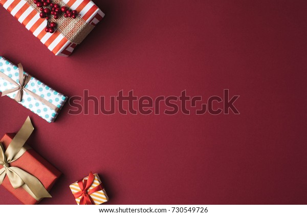 top view of arranged wrapped christmas gift boxes with ribbons on red tabletop