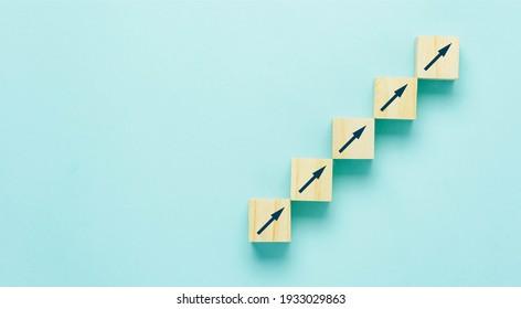 Der Pfeil nach oben geht auf Holzblock stapelend, wie Treppenstufen auf blauem Papierhintergrund, Business Growth Up Konzept. Kopienraum für Text. Abstrakter Erfolgsmarkt . Managementleistung.