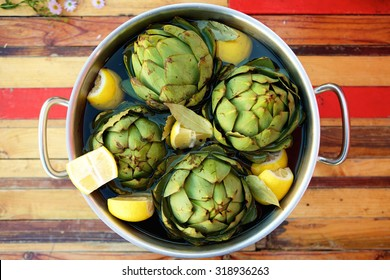 Top view artichokes and lemons in a pot ready to be steamed