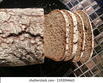 Top view of artisan brown bread loaf on a black plate with four pieces cut off. Flat lay close-up photo on the subject of healthy food.
