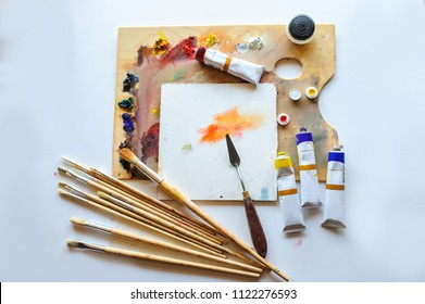 Top view of artist painter workplace: brushes colour painter and used palette
