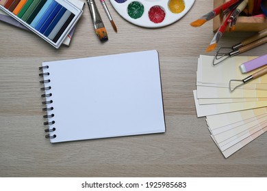 Top view of Artist workspace on wooden background with sketchbook, watercolor, brushes pencils and crayons. Drawing class education.
