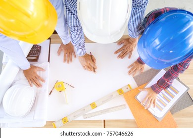 Top view of asian architect and engineer team looking blueprint and sketching a new construction building project together, business teamwork concept
