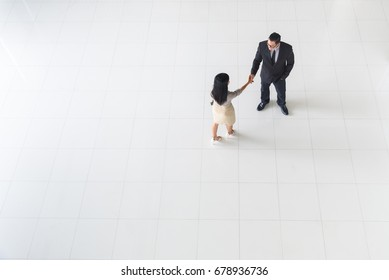Top view, Asian business people, man and woman, greeting by smiling and shaking hands, copy space