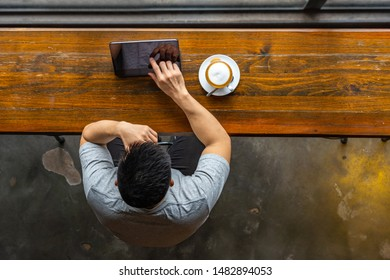 Top view of Asian freelancer using tablet at rustic coffeeshop