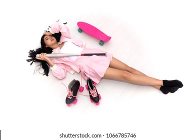 Top view of Asian girl lying down on the floor with many sports equipments around on white background.
