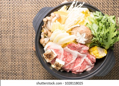 Top view of Asian style hot pot with corn beef, a lot of vegetables, and mushroom on a brown mat.
