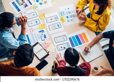 top view asian ux developer and ui designer brainstorming about mobile app interface wireframe design on table with customer brief and color code at modern office.Creative digital development agency