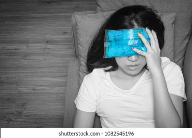 Top view of Asian woman with cold pack on her forehead for relief fever headaches and migraines, black and white tone