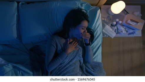 Top view of asian woman has illness from colds or flu and sore throat on bed at night