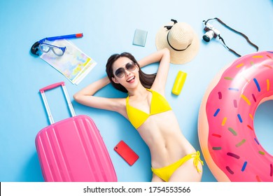 Top view of asian woman is ready to travel wearing bikini swimsuit with luggage and suitcase