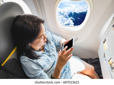 Top view of Asian Woman sitting at window seat in airplane and turn on airplane mode on mobile phone before take off,Black blank screen for adding design
