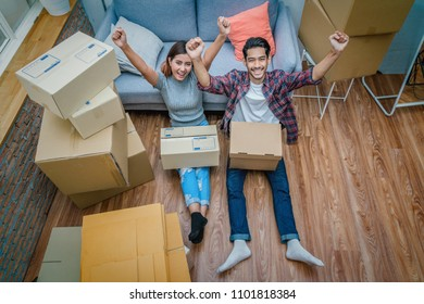 Top view of Asian young couple are glad after successfull packing the cardboard box for moving in new home, Helping relocate and joshing together, Moving and House Hunting concept, selective focus