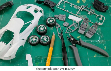 Top view of Assemble car plastic model for hobbyists , scale model of a sport car, Hobby and leisure at home in quarantine.