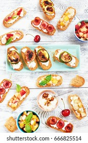 Top view of assorted crostini (toasts) with cut fresh fruits: cherry, peach, pear and grilled figs on white wooden table. Healthy summer picnic snack.