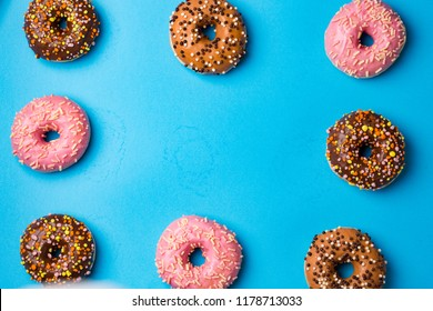 Top view of assorted donuts on blue concrete background with copy space. Colorful donuts background.