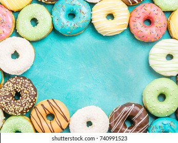 Top view of assorted donuts on blue concrete background with copy space. Colorful donuts background. Various glazed doughnuts with sprinkles.