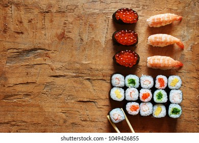 Top view of assorted sushi with ikura, shrimp, omelette, salmon and wakame on wooden table. Copy space.