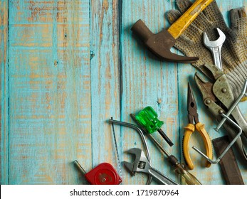 Top view of assorted work tools on wooden background