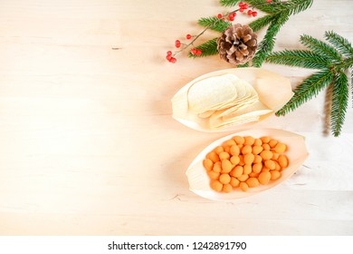 Top view assortiment of snack in bamboo nature bowl in boat shape, on wood board, concept snack for party in christmas holiday with family.