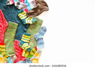 Top view of an assortment of colorful woolen socks of various sizes on white background