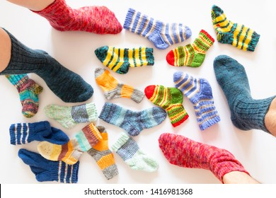 Top view of an assortment of colorful woolen socks of various sizes on white background with two pairs of feet wearing a red and a blue sock