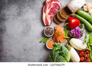 Top view of assortment of healthy balanced food: meat, fish, vegetables, bread, cereals, beans, stone background, space for text. Raw ingredients for cooking healthy meal, good for diet, clean eating
