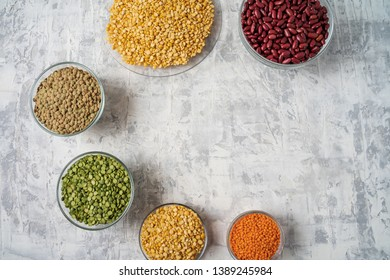 Top view of assortment of peas, lentils, beans and legumes over white background, with copy space.