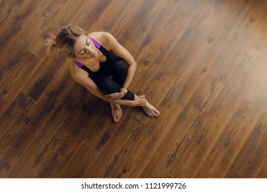 Top view of athletic healthy woman meditating on parquet floor