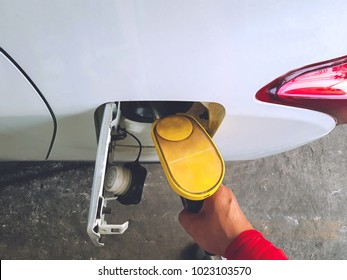 Top view of attendant filling Gasoline to Gas tank of white Car. Man holding the yellow Fuel nozzle refueling fuel at gas station.