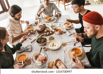 Top view of attractive international friends sitting at the table full of food eating together. Young colleagues having lunch dreamily spending time in cozy cafe