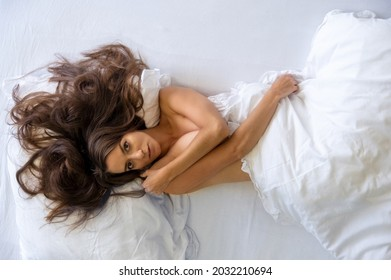 Top view of attractive, young, sexy woman, windblown hair wild on the sheets, relaxing in bed, sunday morning, enjoys fresh soft sheets and mattress in the bedroom, copy space