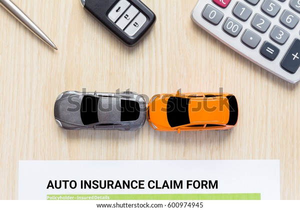 Top view of auto insurance claim form with car toy crash on wooden desk