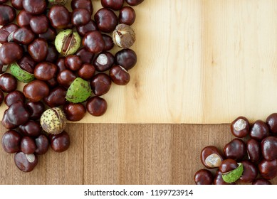 Top view of autumn arrangement with copy space, created from chestnuts on simply wooden background from dark and light wood.