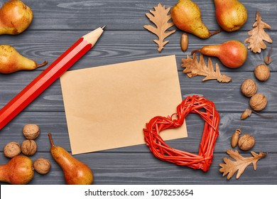 Top view of autumn harvest lying on gray wooden plank background with blank brown sheet with copy space in center, big pencil and heart shape