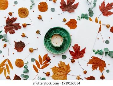 Draufsicht auf Herbstblätter und Tasse Kaffee einzeln auf Weiß