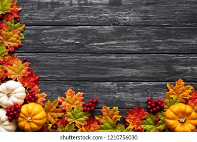 Top view of  Autumn maple leaves with Pumpkin and red berries on old wooden backgound. Thanksgiving day concept.
