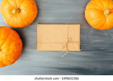 Top view of Autumn orange Pumpkins with gift in brown paper package tied up with strings on old wooden gray background. Thanksgiving and Halloween concept. Copy space for text and design