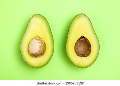 Top view avocado slices fruit on the green background