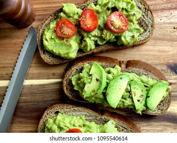Top view of avocado toast on a wood cutting board