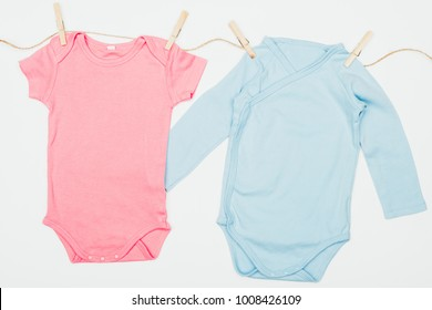 top view of baby bodysuits drying on rope isolated on white