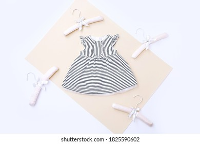 Top view of baby girl dress and hangers around. Baby fashion concept, Sale concept