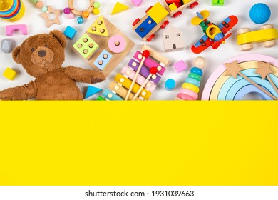 Top view to baby kids toys. Set of colorful educational wooden and fluffy toys and yellow blank background with copy space for text